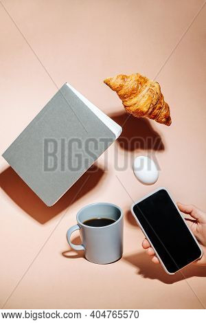 Hand Taking Picture On A Phone. Croissant, Egg And Notebook Hovering In Air