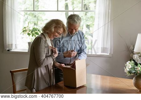 Happy Mature Man And Woman Unpacking Parcel At Home Together