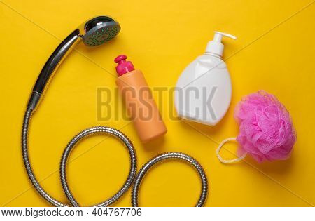 Showering. Shower Head Hose With Bath Sponge, Bottle Of Shower Gel On Yellow Background. Top View