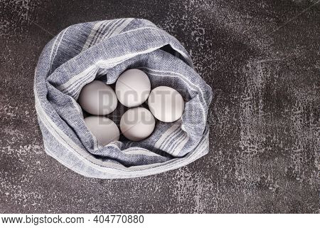 Chicken Wrapped In A Towel Lie Against The Background Of A Shabby Wall. White Rustic Eggs On Gray-bl