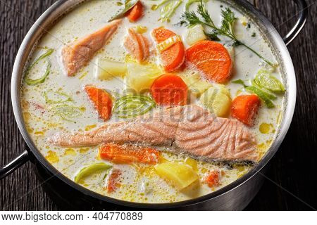Lohikeitto, Salmon Fish Soup With Cream, Potato, Carrots, Leek And Dill In A Pot On A Dark Wooden Ta