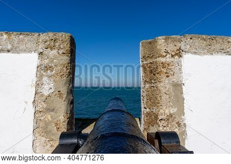 View Of The Old City Wall And Battlements With Historic Cannon In The Harbor Of Cadiz