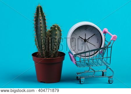 Shopping Time. Supermarket Trolley With Clock And Cactus On Blue Background
