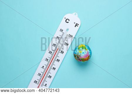 Climate Control. Global Warming. Weather Thermometer With Globe On Blue Pastel Background. Top View