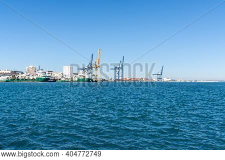 Supply Ships And Harbor Cranes In The Industrial Port In Cadiz
