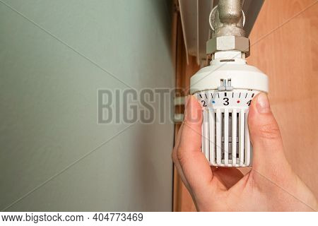 Girl Adjusts The Radiator Valve. Valve From A Heating Radiator. Manual Control Valve Of The Heating