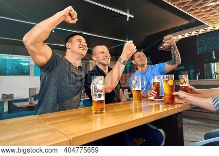 Happy Friends Sitting In Pub And Watching Football Match Together. Male Friends Cheering Laughing An