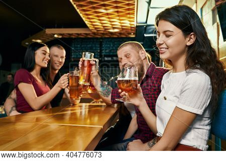 Side View Of Young Smiling Brunette Enjoying Free Time With Happy Friends And Drinking Beer In Bar.
