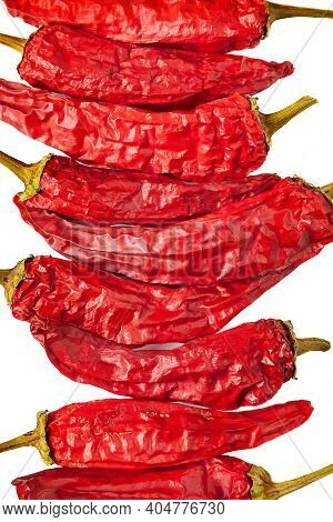 Close-up Of A Red Pepper. Dry Peppers Are Grouped On A White Background. Hot Chili Peppers. Spices F