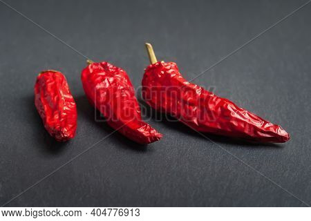 Red Pepper. Three Red Dry Peppers Stacked On A Black Slate Stone. Hot Chili Peppers. Spices For Cook