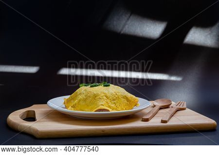 Omelette In White Plate Isolated On Black Background.