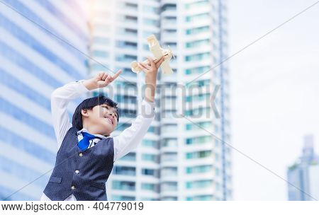 Handsome Business Little Boy Holding Model Airplane In City With Happy And Smile Face. Adorable Litt