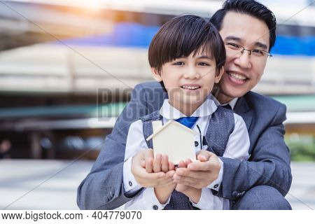 Outdoor Portrait Business Family With House Model Father And Child Holding House In Hands And Want N