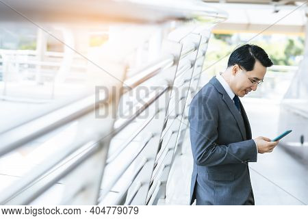 Handsome Asian Businessman Holding Using Smart Phone, Wear Suit And Eyeglasses. Leadership Executive