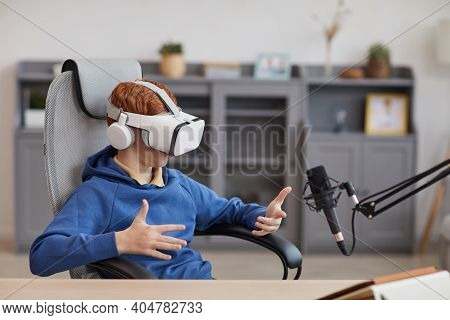 Portrait Of Teenage Boy Wearing Vr Headset And Speaking To Microphone While Playing Immersive Video