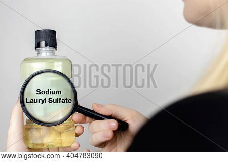 A Woman Examines The Harmful Ingredients Of The Mouthwash. Harmful Composition Of Ingredients. Rinse