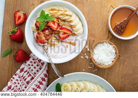 Variety Of Yogurt Bowls With Strawberry And Plain Yogurt, Fruit And Granola