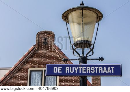 Texel, Netherlands - August, 2013: Little Window With Green Shutters With Street Name Sign And Light