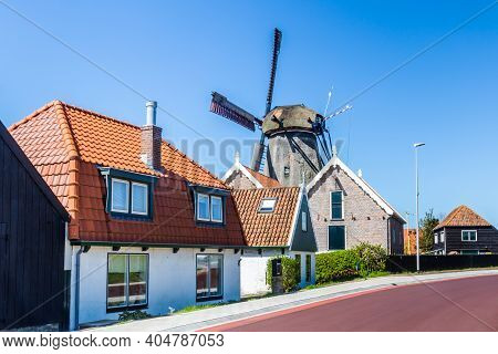 Texel, Netherlands, May, 2018: Village Oudeschild With Windmill And Trraditional Fisherman Houses On