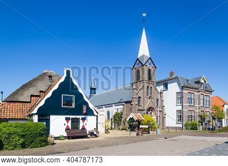 Texel, Netherlands, May, 2018: Village Oudeschild With Martinus Church And Trraditional Gable Houses