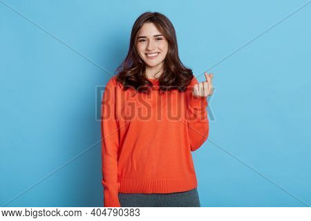 Cheerful Young Woman Makes Korean Like Sign, Demonstrates Her Liking, Expressing Love,shows Heart Ge