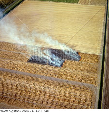 Zijpe, Holland, April 14 - 1988: Historical aerial photo of controlled burning down the agriculture fields in springtime in the northern part of Holland