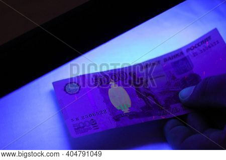 Verifying The Authenticity Of Money In Ultraviolet Light. 5000 Rubles Paper Currency Of Russia Under