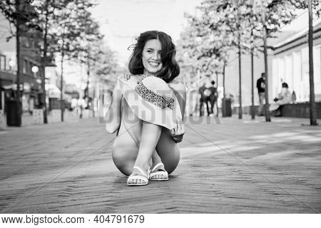 Bare Young Woman In Hat Sitting At City On Cobblestone, Monochrome