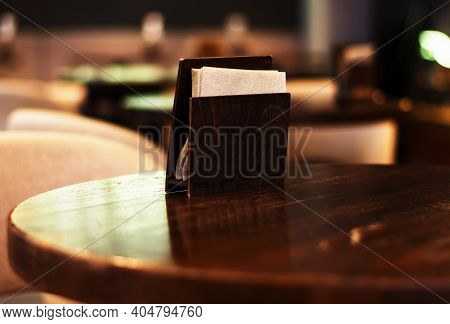 Selective Focus, Holder For Napkins On A Wooden Table In A Cafe. Blurred Background. Copy Space.