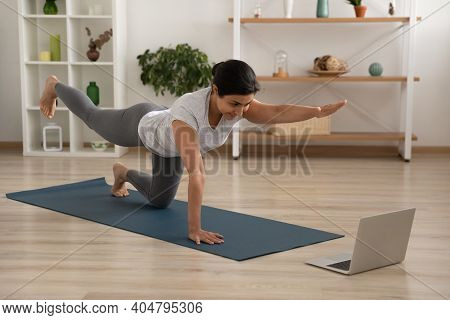 Active Indian Female Practice Static Tiger Asana Look At Laptop