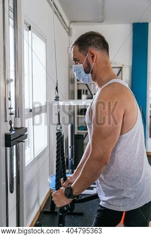 A Man Doing Triceps Exercises In The Gym. Looking At The Camera. Health And Wellness Concept