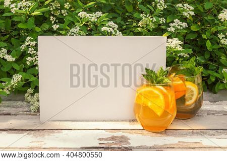 Summer Orange Lemonade In Glasses And Empty Card For Your Text On Rustic Wooden Table On Fresh White