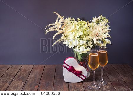 White Beautiful Astilbe And Hydrangea Flowers, Glasses Of Champagne And Heart Shape Gift Box On Wood