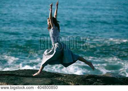 An dancer is engaged in choreography on the rocky coast of Atlantic ocean in Portugal.