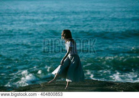 Dancer is engaged in choreography on the rocky coast of Atlantic ocean in Portugal.