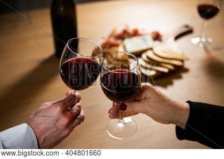 Making A Toast By Clinking Two Glasses With Red Wine.