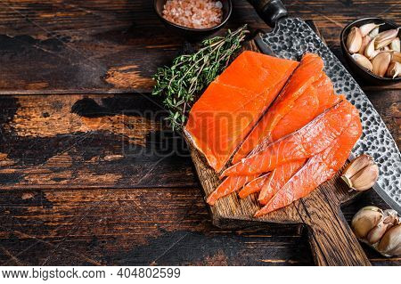 Sliced Smoked Salmon Fillet On A Wooden Cutting Board With Herbs. Dark Wooden Background. Top View.