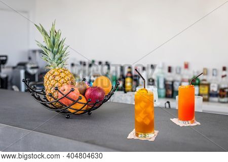 Alcohol Blurred Bottles Bar Counter, Cocktail Glasses On The Bar Counter With Fresh Fruits Decoratio