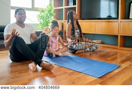 Portrait Of Family Doing Yoga Exercise While