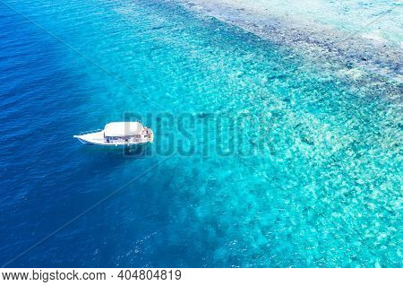 Top View Of A White Boat Sailing In The Blue Sea. Speedboat With Tourists, Snorkeling And Diving Out