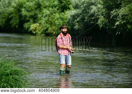 Man Fishing And Relaxing While Enjoying Hobby. A Fisherman With Fishing Rod On The River. Fisherman