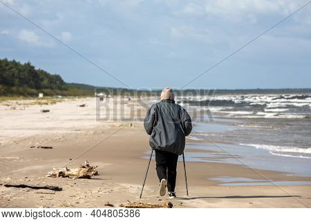 Active Mature Lifestyle. Senior Nordic Walking On A Sandy Beach Sea Shore