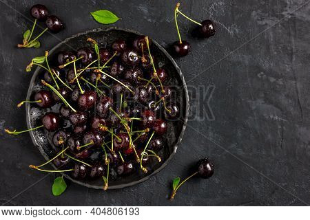 Fresh Sour Cherries In A Black Bowl On The Dark Background With Copy Space For Text. Fresh Ripe Sour