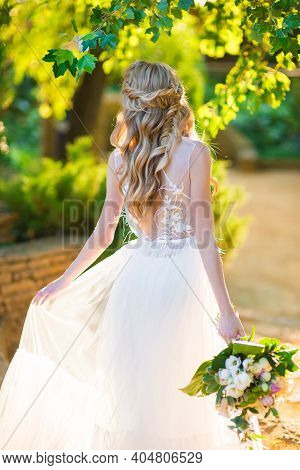 Beautiful Bride With A Bridal Hairstyle And A Bridal Bouquet In The Back In A Green Garden