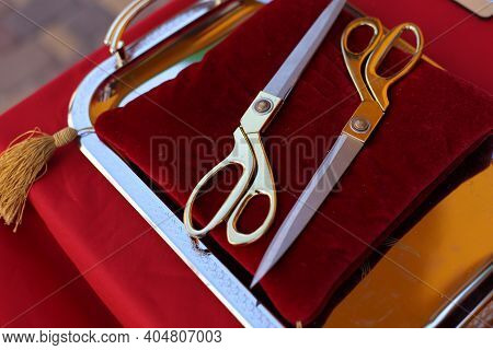 Gilded Scissors On Red Cushion For Cutting The Ribbon For The Opening Ceremony. Golden Scissors For