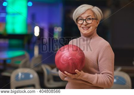 Waist Up Portrait Of Smiling Senior Woman Holding Bowling Ball And Looking At Camera While Enjoying