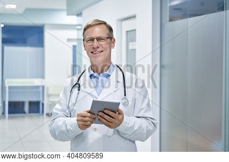 Smiling Old Middle Aged Doctor Holding Using Digital Tablet Standing In Hospital Looking At Camera.