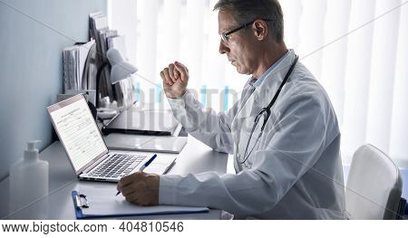 Serious Mature Old Doctor Physician Using Laptop Tech In Hospital Office. Senior Middle Aged Male Gp