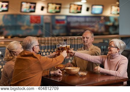 Group Of Smiling Senior People Drinking Beer In Bar And Clinking Glasses While Enjoying Night Out Wi