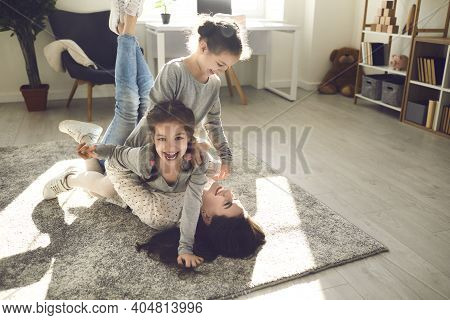 Happy Mother And Cute Little Children Playing And Laughing On A Warm Rug At Home
